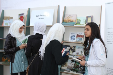 A group of young adults visiting Tamer's booth at the international Palestine book fair 2014. Photo: Tamer Institute